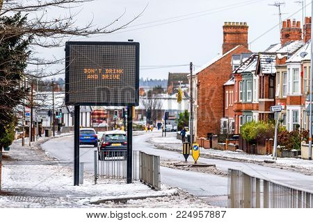 Cloudy Day Winter View of modern information sign with words Do Not Drink and Drive on Typical English road under snow.