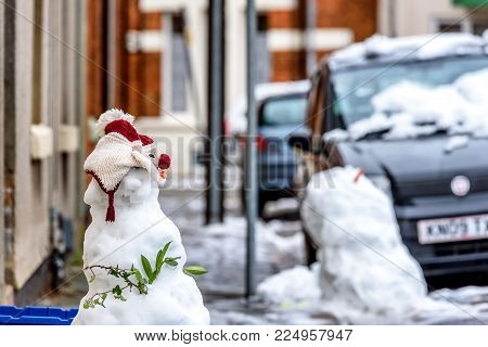Cloudy winter day view of homemade snowman on typical british road footpath next to empty recycling bin boxes.