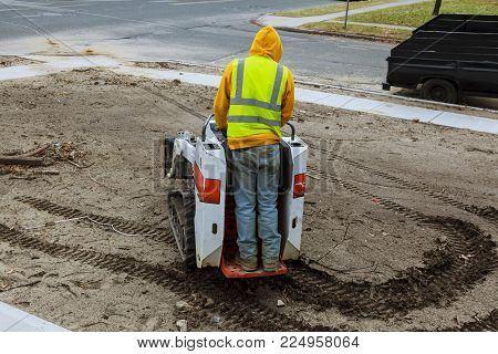A small excavator works on the street in the summer small excavator Bobcat at construction site