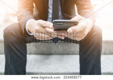 Businessman touching phone outside on stair in freetime by surf internet and social media and use internet for shopping online