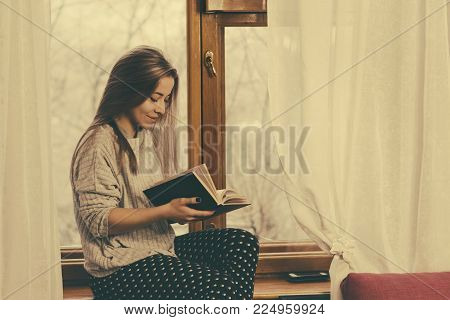 Sweet girl reading a book sitting on the windowsill. Pleasant pastime. Self-education at home.
