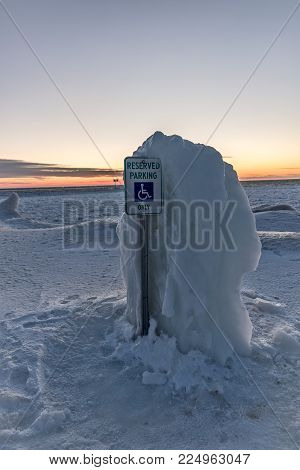 Thick ice taller than the parking sign is protecting the handicap parking space at the edge of Lake Michigan