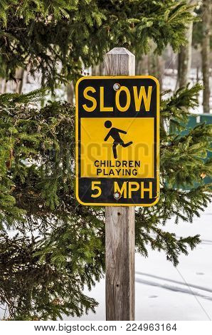 Yellow and black sign to warn drivers that children might be playing in the road.  Slow down!
