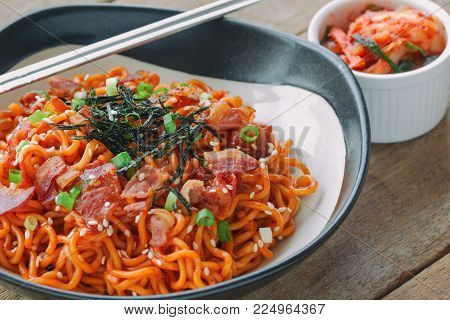 Korean hot and spicy instant noodle in black bowl. Spicy noodles topped with bacon, sesame, seaweed and chopped scallion served with kimchi on wood table with copy space. Homemade delicious Korean food concept. Instant spicy noodle in Korean style.