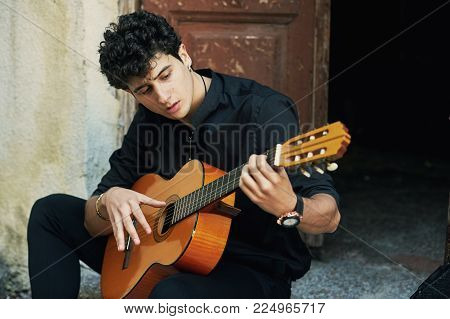 Young man playing guitar in the yard . Street musician