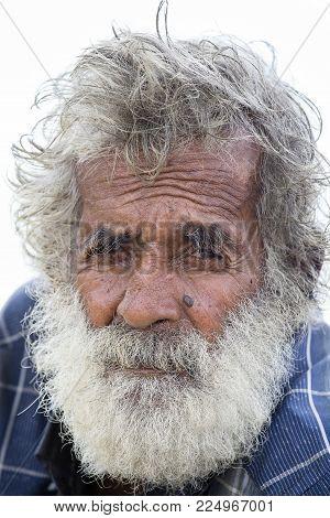 MATARA, SRI LANKA - NOVEMBER 5, 2014: Unidentified old Sri Lankan beggar waits for alms on a street next to the bus station