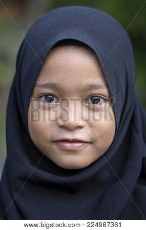 UBUD, BALI, INDONESIA - JANUARY 02, 2018 : Unidentified portrait of a little indonesian muslim girl at the streets in Ubud, island Bali, Indonesia, close up