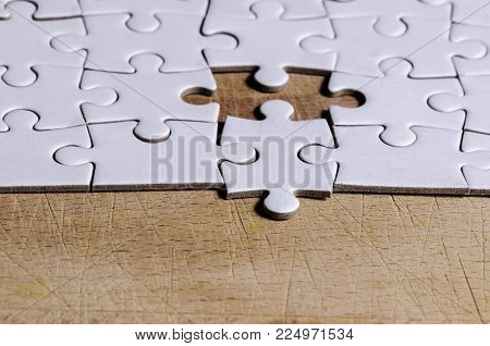 white jigsaw/puzzle with one piece at wrong position, over  black wooden table background, symbol of problem solving and new vision