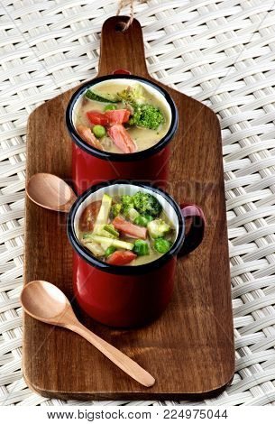Delicious Vegetables Creamy Soup with Broccoli, Carrots, Zucchini, Leek, Red Bell Pepper and Green Pea in Red Soup Cups with Wooden Spoon closeup on Wooden Cutting Board