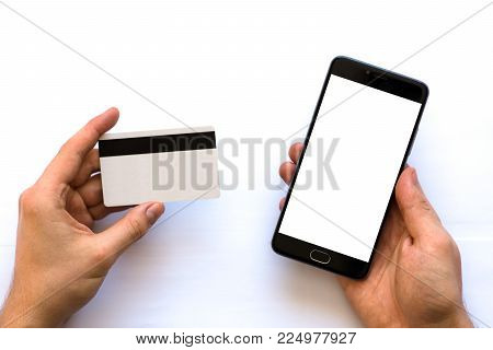 A black smartphone mock up and a credit card in the hands of a man on a rural white background, concepts of Internet commerce and the use of online banking to pay for services and goods in Internet