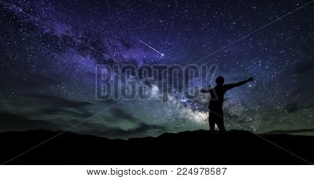 The milky Way with the man on the mountain. Landscape with night sky with stars and the silhouette of a happy man standing with outstretched arms. shooting star. Galaxy. Brightest falling star