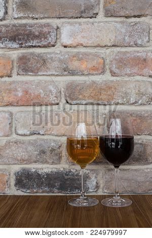Glasses with red and white wine. Red and white wine glasses on a old brick wall copy space.