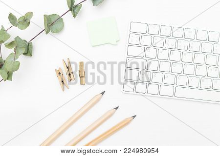 Keyboard and office supplies on a white background. Flat lay