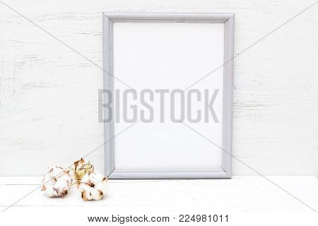 Gray frame and cotton flower on a white wooden background. Mininmalist