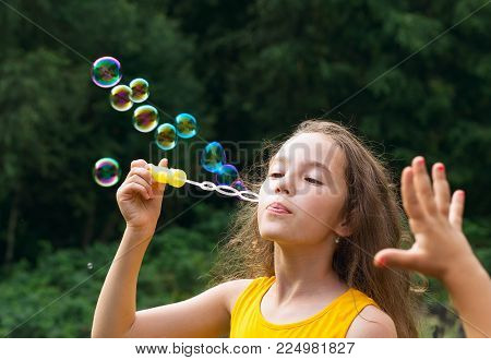 Cute Little Girl blowing soap bubbles outdoor at summer day - happy childhood