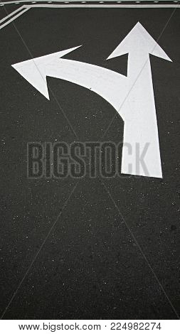 Moving in the right and straight direction white arrow symbol as traffic sign on asphalt road for motion directing toward the successful future represented.