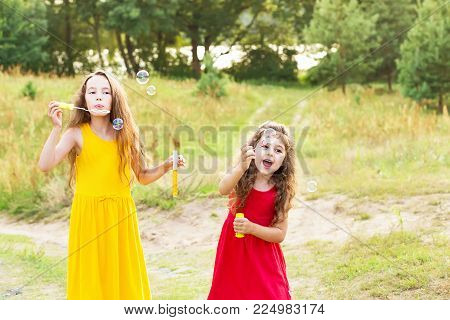 Two Cute Little Girsl blowing soap bubbles outdoor at sanny  summer day - happy childhood