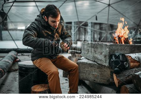 Stalker, male person eating against fireplace