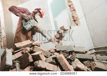worker with demolition hammer breaking interior wall