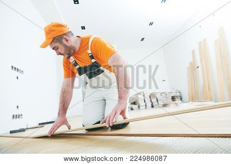 worker joining parket floor. slow motion