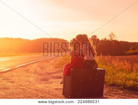 Silhouette of two little girls sitting at vintage suitcase on the road at sunset. Sisters enjoyed a Holiday over blurred summer nature.