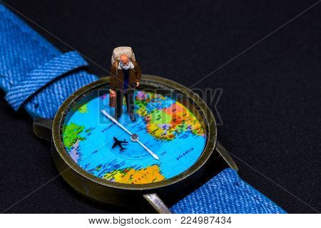 Old man with backpack and world map watches. Around world travel photo banner. Senior traveler figurine. Retired backpacker travel. Lifetime traveller. Travelling around world concept. Aged traveler