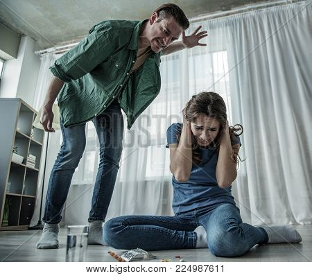 Low angle of scared young woman sitting on floor and covering her head for protection. Aggressive man is going to hit her. Pills are on floor