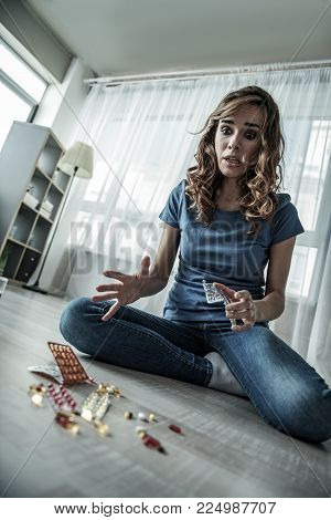 Low angle of hysteric young woman looking at various medications with panic. Suicide concept