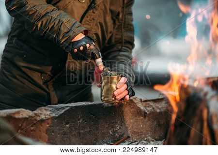 Stalker, male person cooking canned food on fire