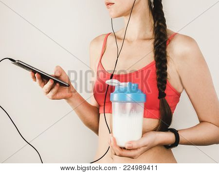 Stylish woman studying the results of her workout using a smartphone. Sport, fitness, health