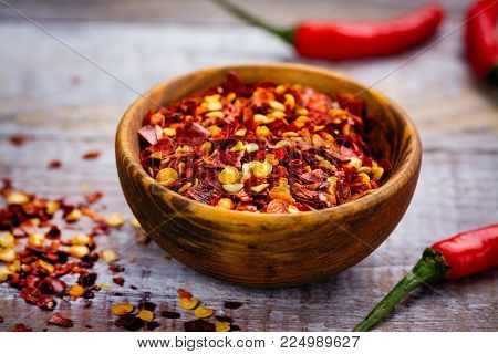 Red hot pepper flakes in a wooden mortar and pepper pods on wooden table. Copy space
