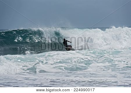 PUERTO VIEJO, COSTA RICA-MARCH 19, 2017: Surfer on the beach near Puerto Viejo, Costa Rica