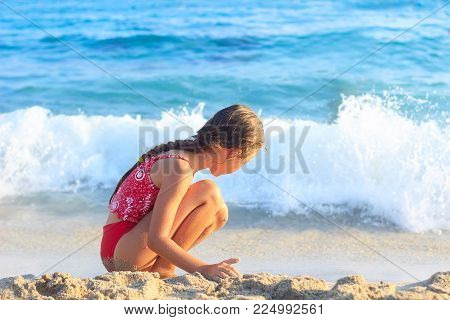 Happy Little Girl playing with sand by the Sea Waves.  Summer Sunny Day, Ocean Coast