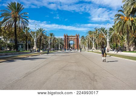 BARCELONA, SPAIN - OCTOBER 22, 2015: The Arc de Triomf  is a triumphal arch in the city of Barcelona in Catalonia, Spain. The arch is built in reddish brickwork in the Neo-Mudejar style