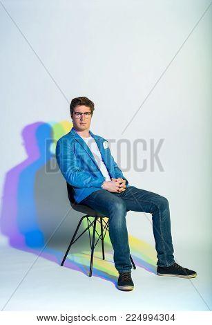 Full length portrait of serene man sitting on chair. Composure concept