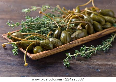 Canned capers and thyme on a wooden table .