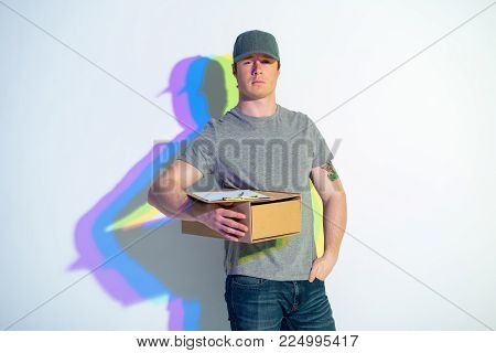 Portrait of calm courier with multicolored shadow keeping parcel. He putting hand in pocket. Delivery concept