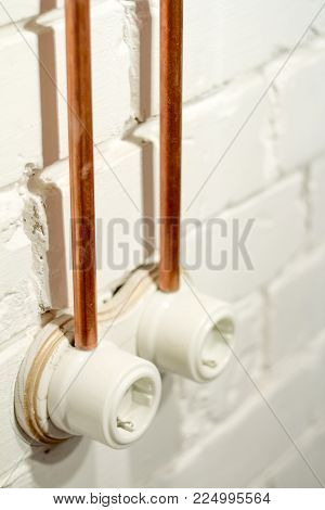 Retro socket made of white ceramic with open electrical wiring. Against the background of a white brick wall, electrical wiring in old copper pipes. Selective focus. There is free space for text.