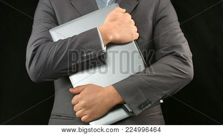 Man in business suit holding laptop computer tight, personal data security HD