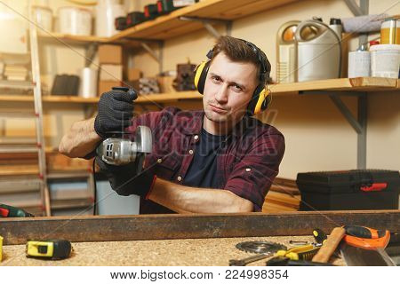 Handsome smiling caucasian young man in plaid shirt, black T-shirt, noise insulated headphones working in carpentry workshop at wooden table place with different tools, sawing iron with power saw