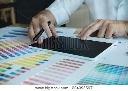 Close up hands male graphic designers,interior designer.Working on graphic tablet in modern space office.discuss data about new start up project of graphics design style and graphics design diagram