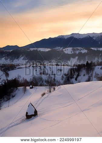 Countryside Landscape With Traditional Romanian Village In The Valleys Of Bucegi Mountains On A Sunn