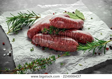 Freshly made raw breed butchers sausages in skins with herbs on crumpled paper
