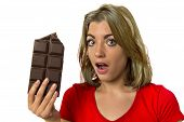 young pretty happy and excited girl holding big chocolate bar in sugar addiction temptation looking guilty skipping diet in unhealthy nutrition lifestyle and overweight concept isolated white background poster