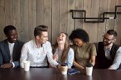 Young man joking at cafe meeting making multiracial friends laugh, diverse people guffaw after guy telling funny comic story during coffee break, happy black and white mates having fun in coffeehouse poster