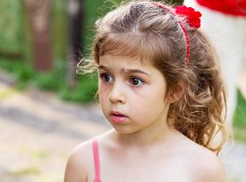 Portrait of  beautiful  little girl looking sad and afraid outdoors