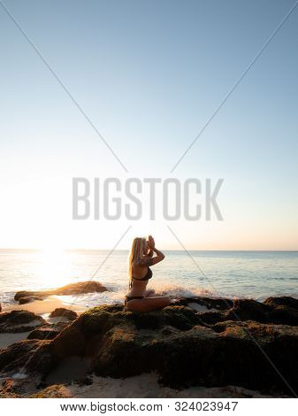 Yoga Concept. Silhouette Of Woman Practicing Yoga, Pranayama On The Beach. Young Woman Sitting On Th