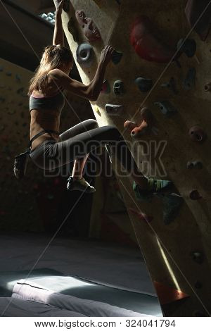 Young Woman Rock Climber Is Climbing At Inside Climbing Gym. Slim Pretty Woman Exercising At Indoor