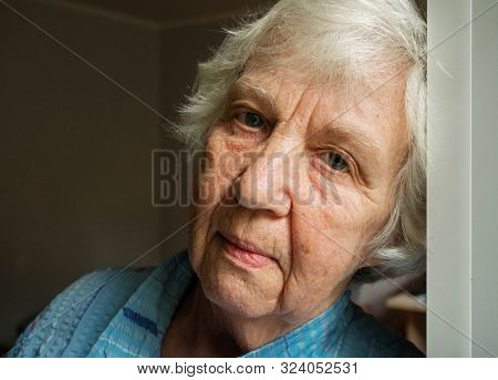 Elderly old gray-haired sad woman face close-up portrait