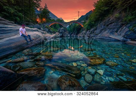Tourist Relaxes At The Verzasca River And Enjoys Colorful Sunset Above The Double Arch Stone Bridge